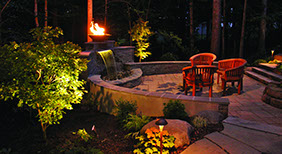 Retaining wall waterfall with fire and patio set at night. Formal Falls.
